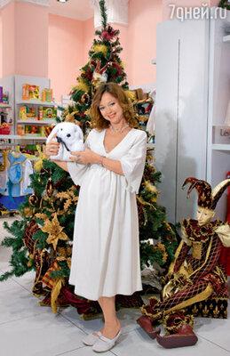 В отделе длябудущих мам актриса присмотрела наряд идля себя. Белое праздничное платье— очень подходящий туалет для встречи года Белого Кролика. Место съемки : салон «Кенгуру»