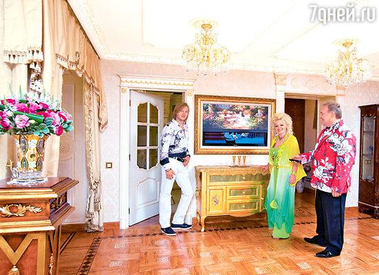 Из технических новинок Кадышева признает лишь телевизор, да и то включает его нечасто. Вот дизайнер и придумал оригинальное решение: плазменный экран скрыт за картиной. Золотистый оттенок паркета из оливы со вставками из оникса сочетается с цветами мебели и отделки