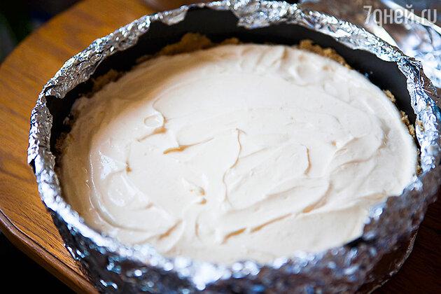 Выложите сырную массу на печенье и разровняйте