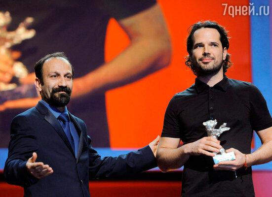 Член жюри, иранский режиссер Асгар Фархади вручает гран-при кинофестиваля венгерскому режиссеру Бенсу Флигафу за фильм «Просто ветер»