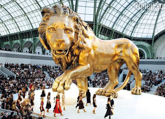 Для дефиле «Chanel» была не только выбрана самая грандиозная площадка— Большой дворец, но и выстроены уникальные декорации (над изготовлением семитонного льва размером 12 метров в высоту и 20 метров в длину 30 скульпторов трудились больше месяца)