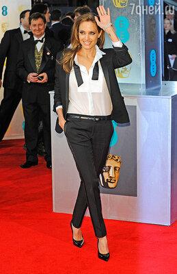 Свой образ, состоявший из прямых брюк и элегантного черного блейзера от Saint Laurent, Анджелина Джоли дополнила лаковыми туфлями-лодочками на высоком каблуке и широкой лентой на шее