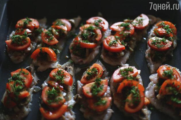 Противень смазываем подсолнечным или оливковым маслом, выкладываем кусочки куриного филе, солим и перчим. Сверху жареные грибы с луком, ломтики помидоров и укроп