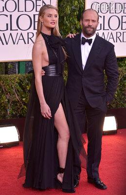 Джейсон Стэтхем (элегантный черный костюм, запонки из коллекции «Martin Katz») позировал фотографам вместе со своей девушкой Роузи Хантингтон-Уитли (платье и туфли «Saint Laurent», собственные серьги, кольца «Dana Rebecca» и «Norman Silverman»)