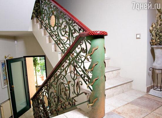 Нарядные кованые лестницы украшены большими медальонами из камня и красными кожаными перилами. Такой кожей обита мебель в гостиной