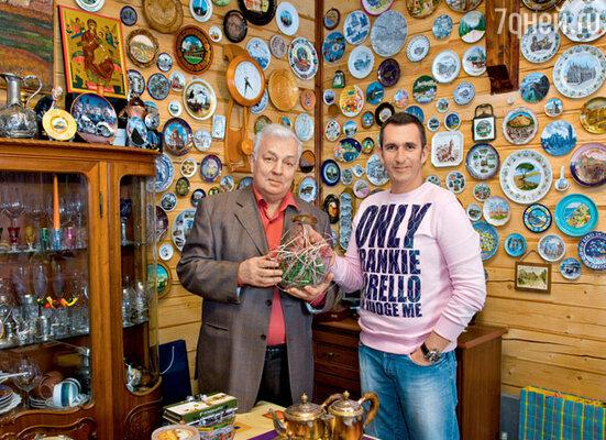 Дядя и племянник на фоне коллекции тарелок, привезенных членами большой семьи из путешествий по странам мира