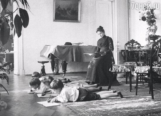 Дети В.Г. Шухова учат уроки, лежа на полу (для правильной осанки), под присмотром гувернантки