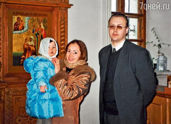 Только что прошедшую обряд крещения Еву держит на руках Наташа. Рядом — Борис