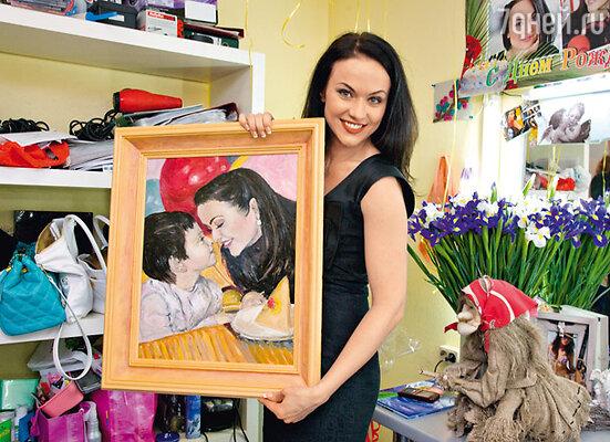 С одним из подарков. На картине — Маша с сыном Никитой