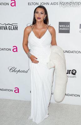 Беременная Ким, несмотря на заметно округлившийся животик, выбрала для пати открытое белое платье Donna Karan