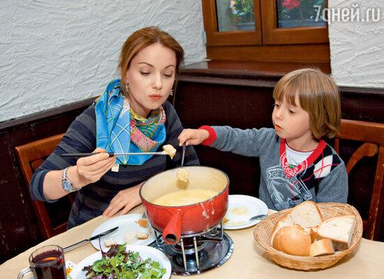 Ольга с Наумом дегустируют швейцарское национальное блюдо — сырное фондю (На Ольге джемпер Sonia Rykiel, на Науме джемпер GF Ferre (кенгуру)