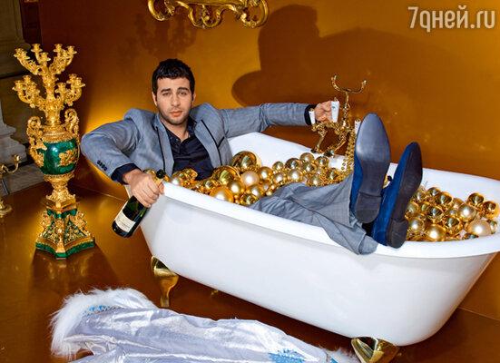 «Не пытайтесь проделать этот трюк дома! Поверьте, моя жена до сих пор находит осколки елочных игрушек в самых неожиданных местах». (На Иване Урганте рубашка Maison Martin Margiela, костюм Byblos, Ботинки Iceberg. Место съемки - инсталляция «Золотая ванная сибарита»(КСМ)