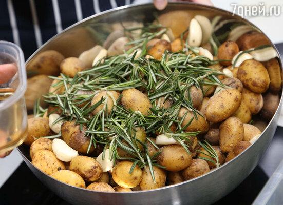 Предварительно замариновать чистый маленький картофель с кожурой: полить оливковым маслом, посыпать свежим розмарином, посолить, уложить рядом 10 зубчиков придавленного чеснока