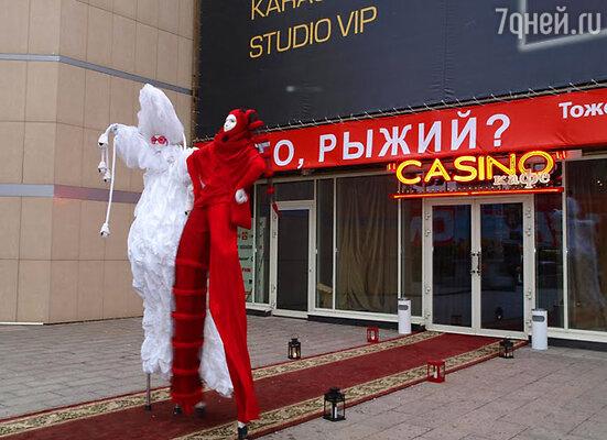 Перед рестораном прогуливались артисты на ходулях, разодетые в яркие костюмы
