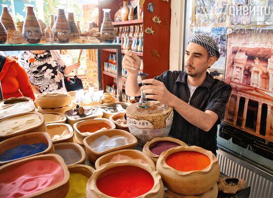 Окрашенный в разные цвета иорданский песок превращается в руках местных мастеров в фирменные объемные картинки «Привет из Петры», заточенные в стеклянные сосуды