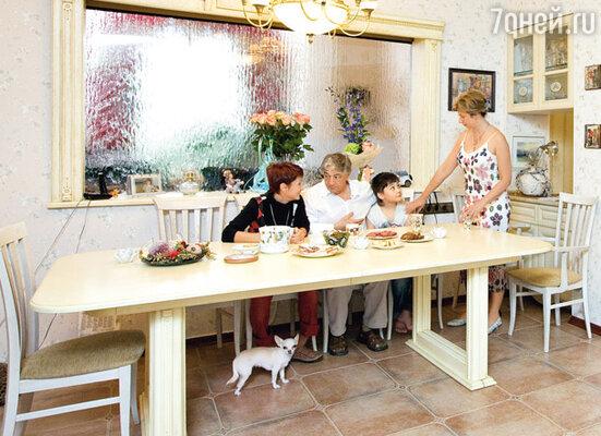 За большим столом-трансформером, если надо, могут уместиться три десятка гостей. А искусственный водопад на стекле, разделяющем столовую и каминный зал, создает ощущение умиротворенности... Писатель с дочерью, женой и внуком Эдиком