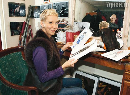 Татьяна Лазарева рассматривает эскизы костюмов