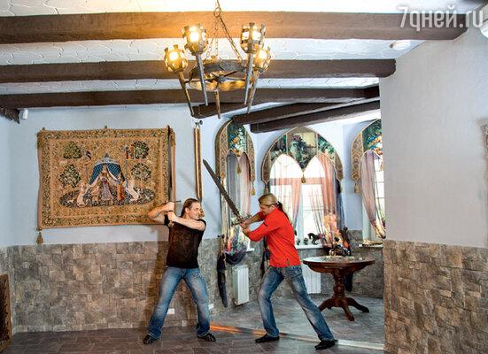 Кованые люстры в виде средневековых факелов в загородном коттедже Эдгарда и Аскольда Запашных полностью соответствуют «рыцарскому» стилю дома