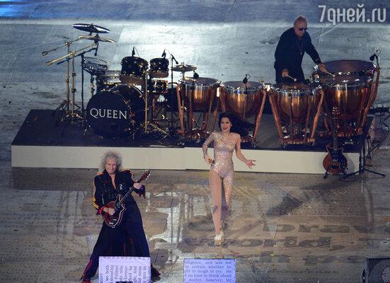 Участники группы Queen Брайан Мэй (слева), Роджер Тэйлор (на втором плане) и певица Джесси Джей