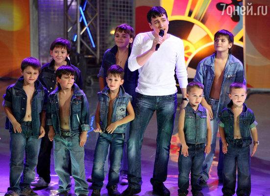 Юра Шатунов появился в окружении хоровода светловолосых мальчишек, одетых точь-в-точь, как их ласково-майский предводитель