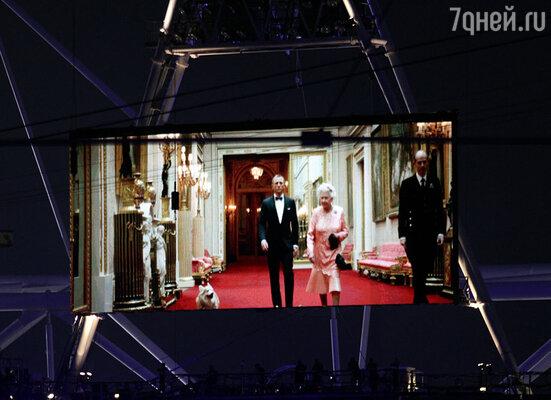 Над стадионом под музыкальную тему «бондианы» появился вертолет, с которого спустились два парашютиста в костюмах королевы Елизаветы II и агента 007 Джеймса Бонда