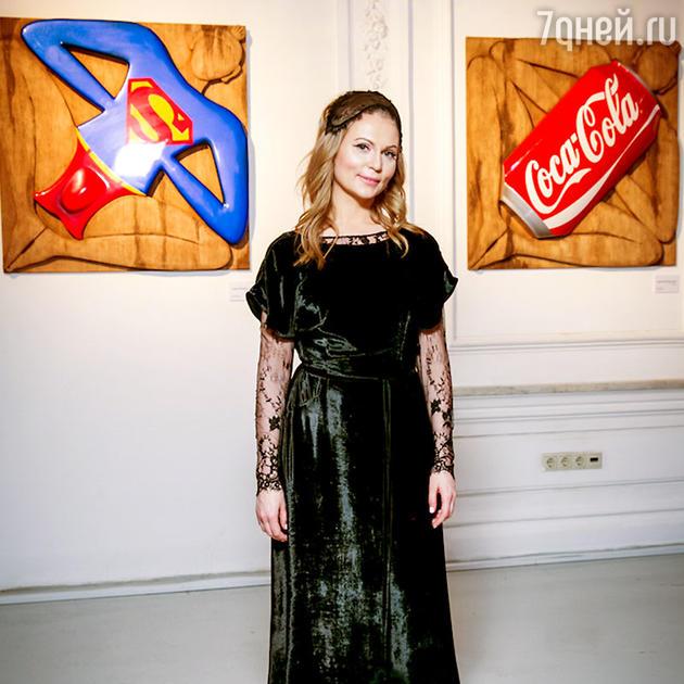Ольга Ломака на фоне своих картин