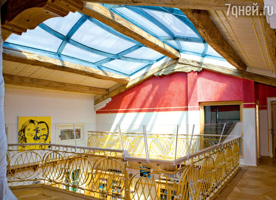 Уютная светлая галерея верхнего этажа дома со стеклянным потолком