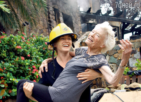 Кейт и 90-летняя мать сэра Ричарда Брэнсона Ева на фоне пепелища изображают ночную сцену, когда Уинслет вынесла старушку из горящего дома. 23августа 2011 г.