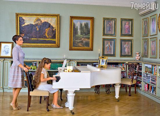 Рояль, встроенная библиотека икартины — неотъемлемая часть гостиной в классическом стиле