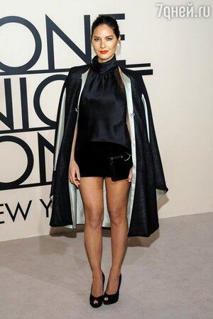Оливия Манн приехала на вечер в шелковом черном топе с воротникой-стойком и в мини-юбке
