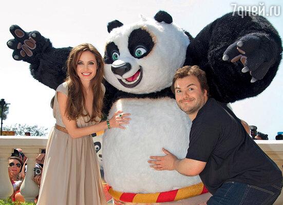 Анджелина с Джеком Блэком и медвежонком По позируют фотографам на набережной Круазетт по случаю презентации внеконкурсного анимационного фильма «Кунг-фу Панда-2». Канн, 12 мая 2011 г.