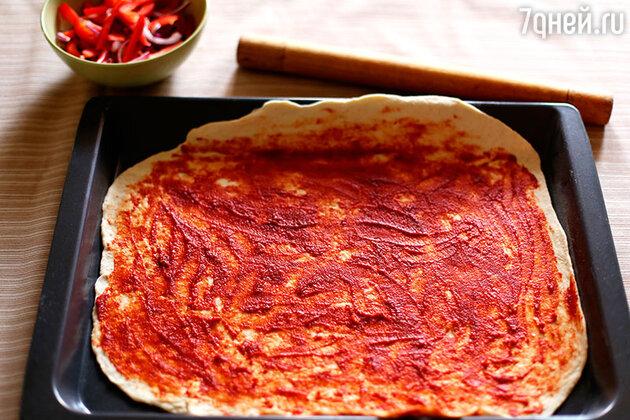 Переносим раскатанное тесто на противень. По нему размазываем томатную пасту