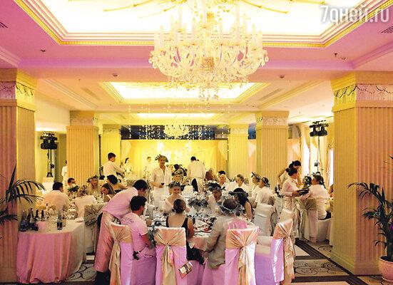 Гирлянды из орхидей, свисающие с потолка, сложные цветочные композиции на столах, стулья в бело-золотых чехлах, античные колонны и декорации, расписанные по мотивам греческих мифов, — таким предстал гостям зал для торжества