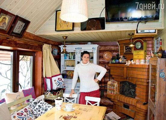 В интерьере этого домика-бани продумана каждая мелочь: узор на подушках и шторах вышит вручную, кованые решетки на окнах и резные наличники тоже сделаны по специальному заказу